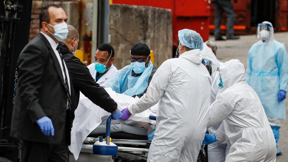 A body wrapped in plastic that was unloaded from a refrigerated truck is handled by medical workers wearing personal protective equipment due to COVID-19 concerns, Tuesday, March 31, 2020, at Brooklyn Hospital Center in New York. (AP Photo/John Minchillo)