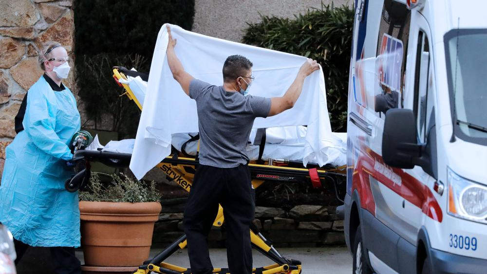In this Feb. 29, 2020, file photo, a person is taken by a stretcher to an ambulance from a nursing facility where more than 50 people were sick and being tested for COVID-19 virus, in Kirkland, Wash.  (AP Photo/Elaine Thompson)