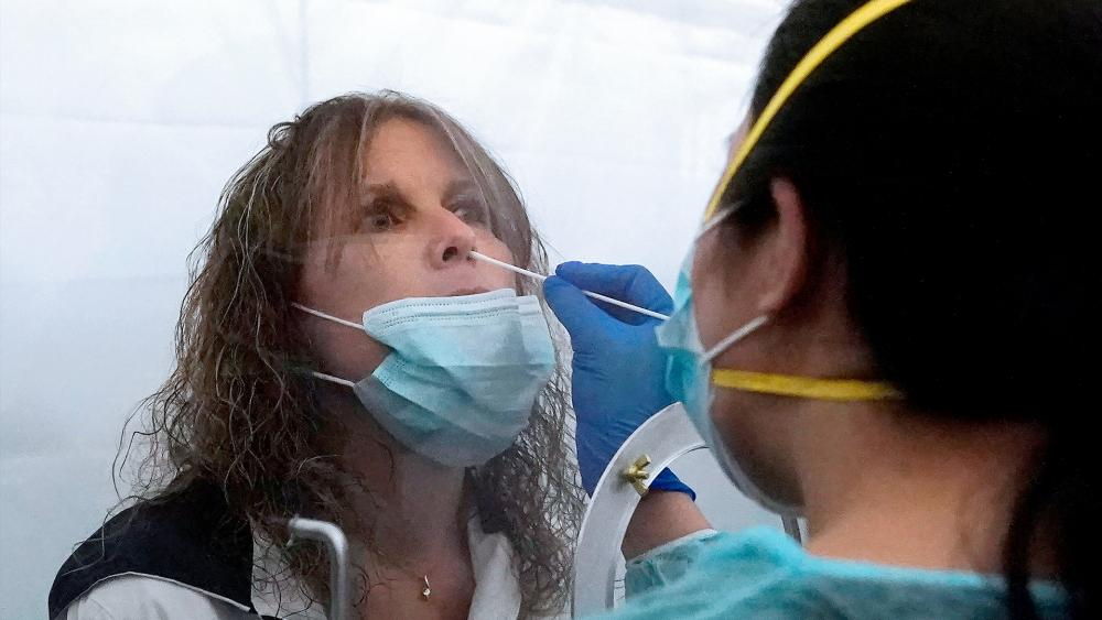 Theresa Zoller gets a rapid COVID-19 test from June Lopez, Dignity GoHealth medical assistant, before a United Airlines flight to Hawaii at San Francisco International Airport in San Francisco, Oct. 15, 2020. (AP Photo/Jeff Chiu)