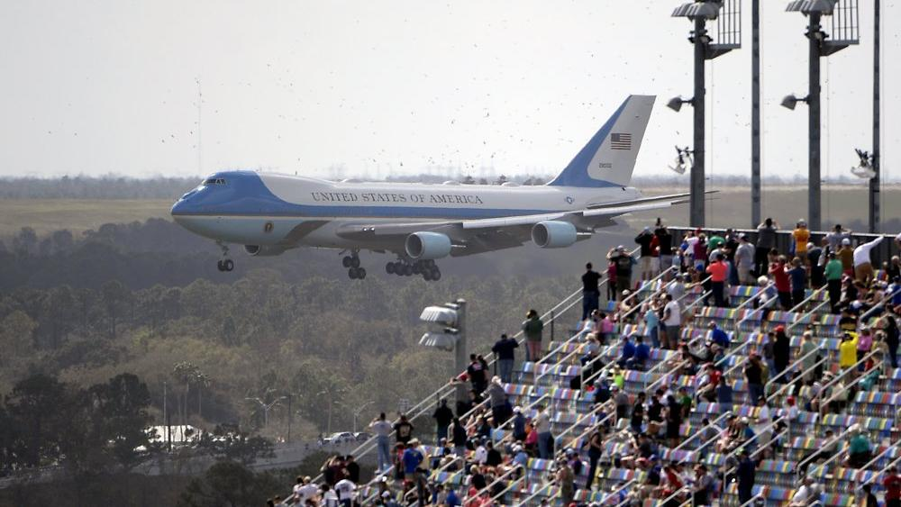 Fans watch from the grandstands as Air Force One, carrying President Donald Trump, prepares to land at Daytona International Airport (AP Photo/Phelan M. Ebenhack)