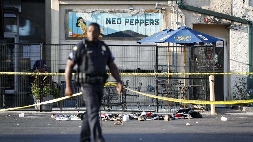 Shoes are piled outside the scene of a mass shooting including Ned Peppers bar, Sunday, Aug. 4, 2019, in Dayton, Ohio (AP Photo/John Minchillo)