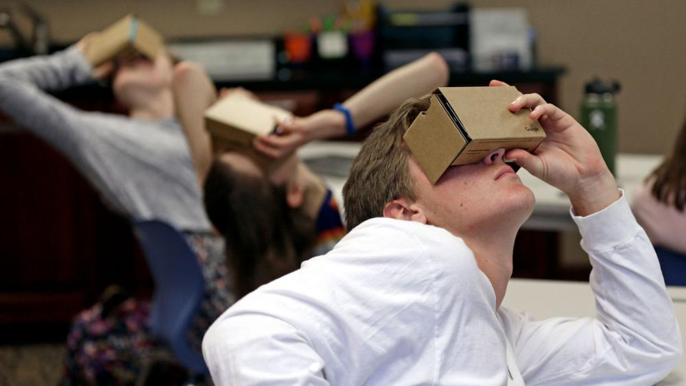 In this photo taken Tuesday, May 21, 2019, photo, Zane Taylor and other students use virtual reality technology to learn about the D-Day invasion at Normandy during a history class at Crossroads FLEX school in Cary, N.C. (AP Photo/Gerry Broome)