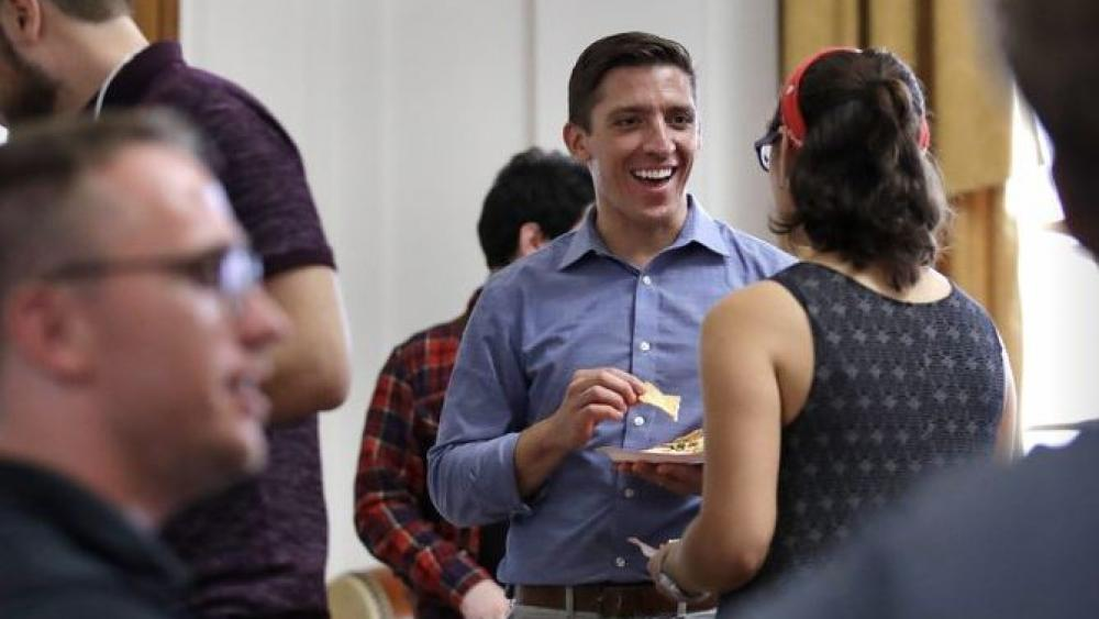 Zak Ringlestein, center, a Democratic candidate for the U.S. Senate, a potluck dinner prior to a meeting of the Southern Maine Democratic Socialists of America at City Hall in Portland, Maine.