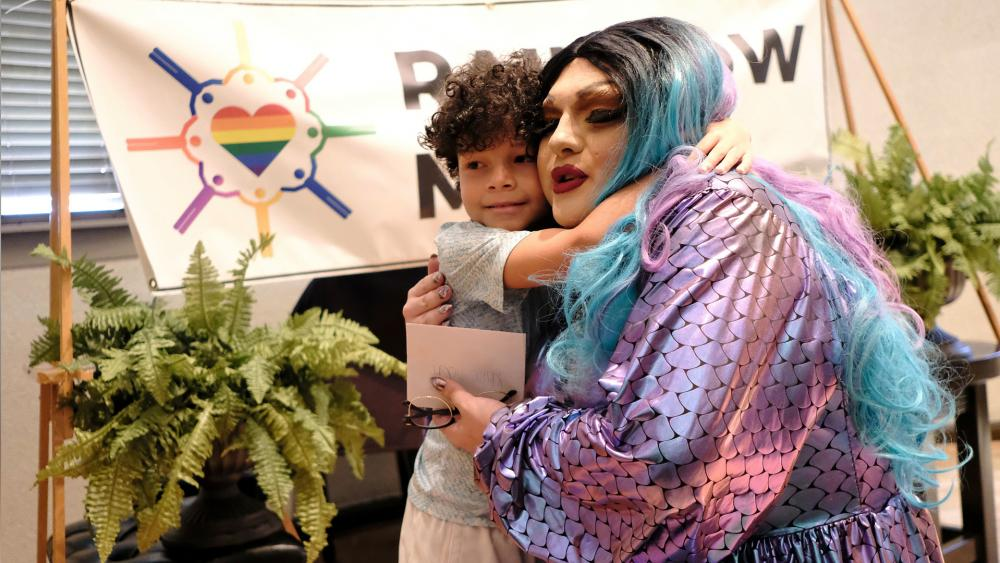 A young child embraces a drag queen at the Mobile Public Library during Drag Queen Story Hour in Mobile, Ala. The event was sponsored by LGBT group Rainbow Mobile. (AP Photo/Dan Anderson)