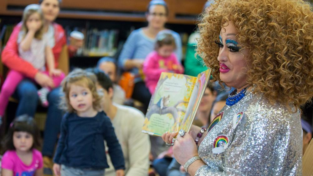 Drag queen story hours have been cropping up in community libraries in recent years like this one in 2017 in Brooklyn, N.Y.  Now a major health insurer has featured a drag queen event with kids in a TV commercial. (AP Photo)