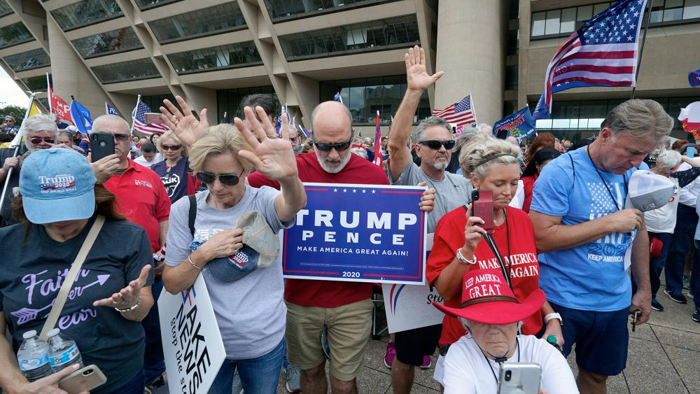 Supporters of President Donald Trump pray during a rally in front of City Hall in Dallas, Saturday, Nov. 14, 2020. (AP Photo/LM Otero)