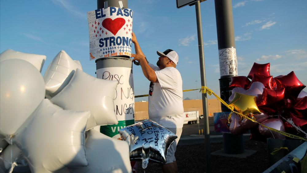 """In this Aug. 6, 2019 file photo, a man hangs up an """"El Paso Strong"""" sign at a makeshift memorial at the scene of a mass shooting at a shopping complex in El Paso, Texas.  (AP Photo/John Locher, File)"""