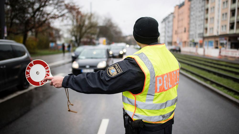 A police officer stops vehicles at a checkpoint in Munich, Germany, March 21, 2020. Newly imposed restrictions require police to question travelers about the reason and necessity of their journey. (Matthias Balk/dpa via AP)