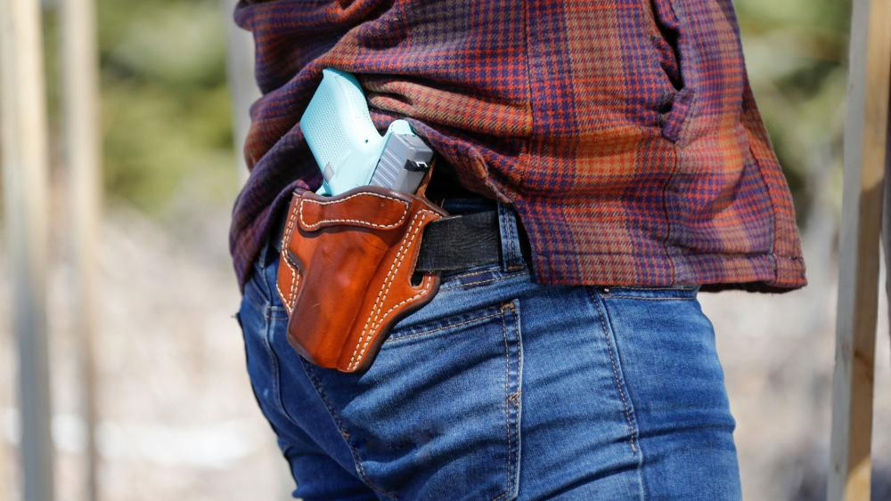 A man carries a firearm in his holster.