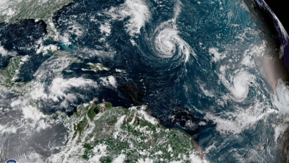 This enhanced satellite image made available by NOAA, shows Tropical Storm Florence, center, in the Atlantic Ocean on Saturday.