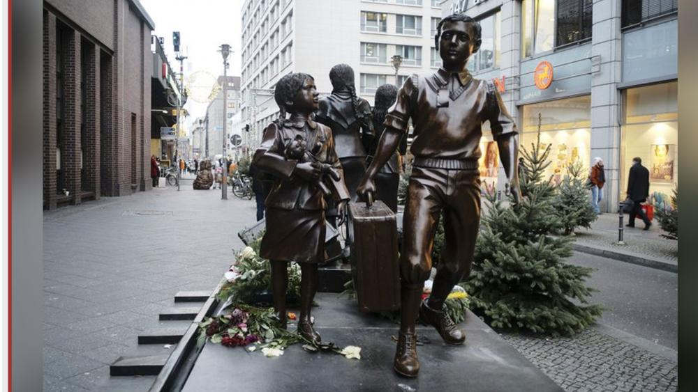 People pass a commemorative memorial statue to perpetuating the memory of the 'Kindertransport' (children transport) near Friedrichstrasse train station in central in Berlin, Germany. AP photo.
