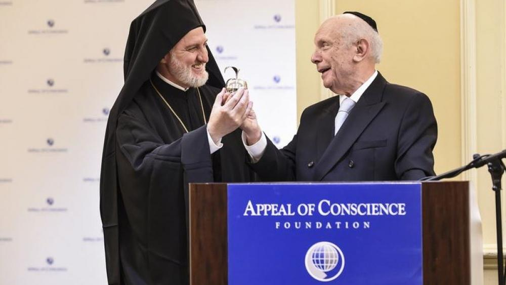 Rabbi Arthur Schneier, senior rabbi of Park East Synagogue, presents a silver apple to welcome Archbishop Elpidophoros, the new leader of the Greek Orthodox Archdiocese of America, to New York, Friday, June 21, 2019.  (Diane Bondareff/AP Image)