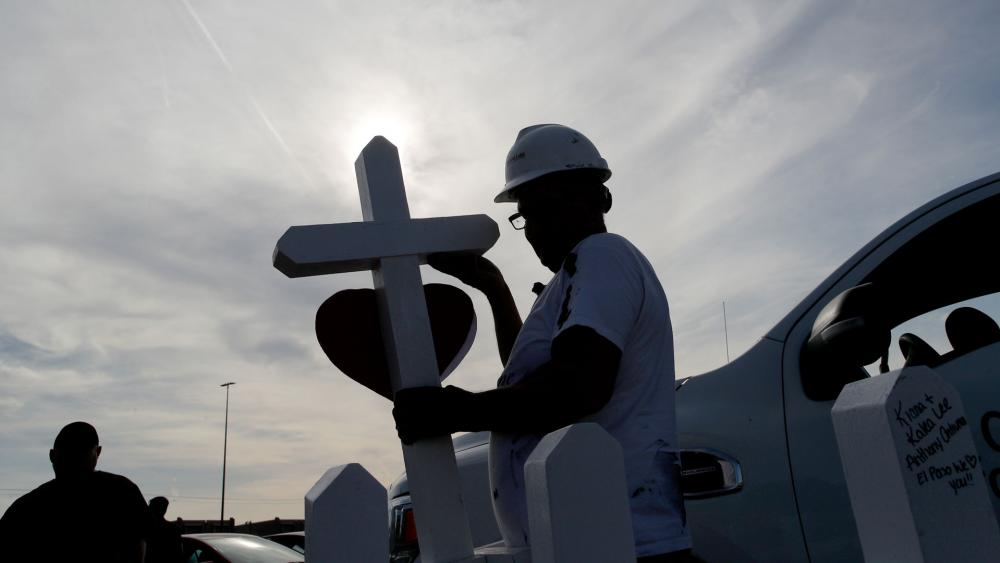 Greg Zanis prepares crosses to place in memory of victims at a makeshift memorial for victims of a mass shooting at a shopping complex Monday, Aug. 5, 2019, in El Paso, Texas. (AP Photo/John Locher)