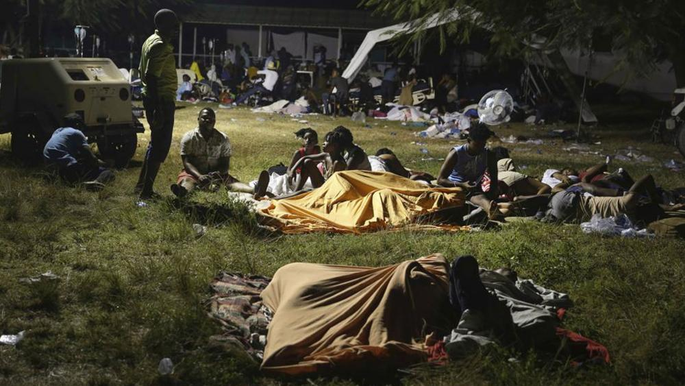 People displaced from their earthquake destroyed homes spend the night outdoors in a grassy area that is part of a hospital in Les Cayes, Haiti. (AP Photo/Joseph Odelyn)