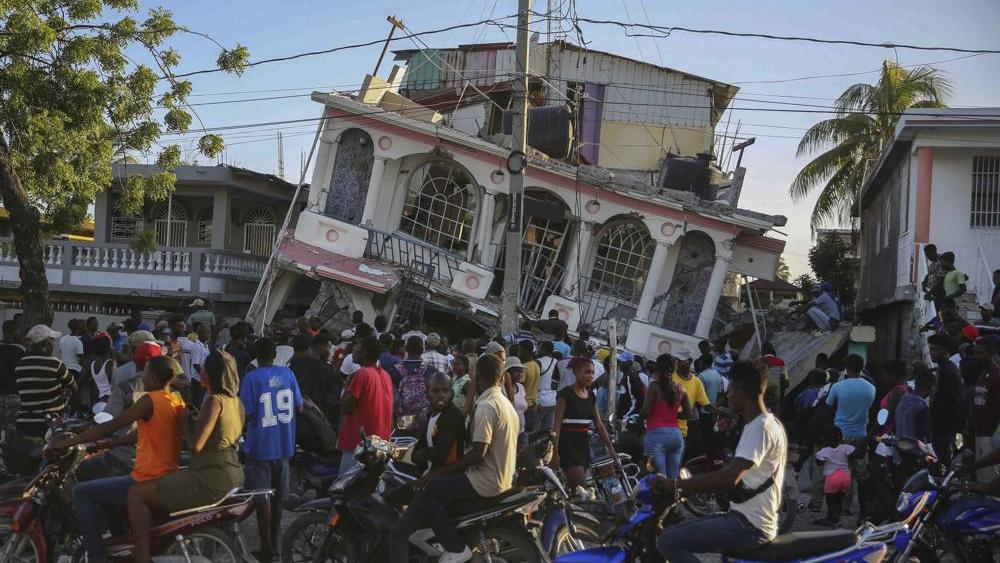 People gather outside the Petit Pas Hotel, destroyed by the earthquake in Les Cayes, Haiti, Saturday, Aug. 14, 2021. (AP Photo/Joseph Odelyn)