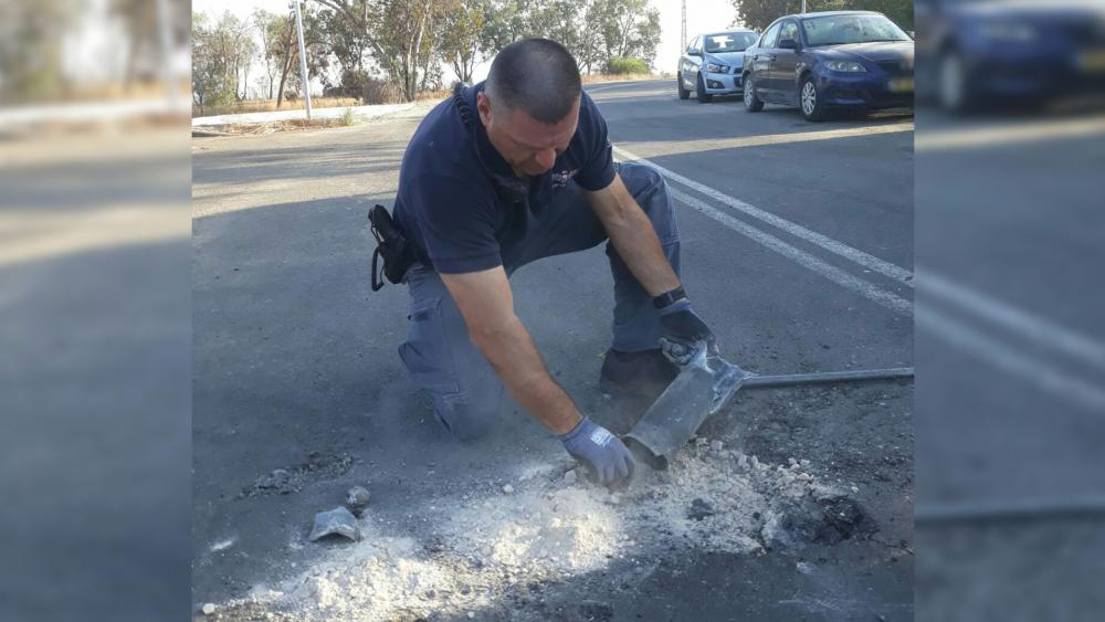 Police Officer Examines Spent Rocket, Photo, Israel Police Spokesman's Office