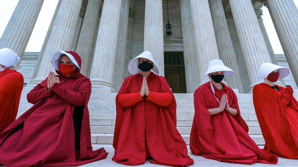 "Activists opposed to the confirmation of President Donald Trump's Supreme Court nominee, Judge Amy Coney Barrett, are dressed as characters from ""The Handmaid's Tale,"" at the Supreme Court on Capitol Hill, Oct. 11, 2020. (AP Photo/J. Scott Applewhite)"