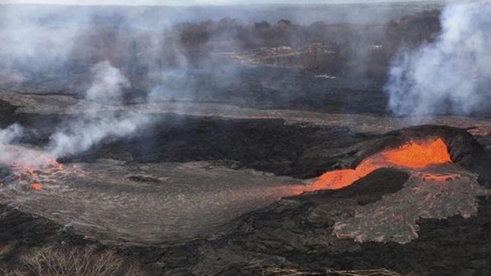 Lava fountains have built a small splatter cone, the black mound at right,  from which lava spills out onto the surface and flows into a small pond at left, in Kilauea Volcano near the town of Pahoa on the island of Hawaii, May 25, 2018.