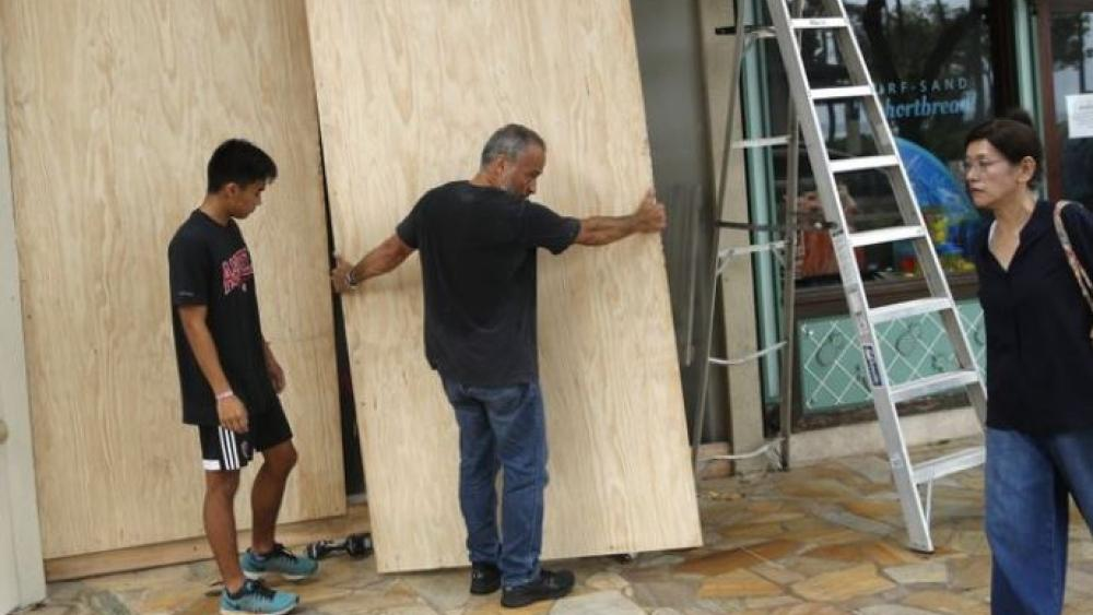 James Fujita, left, and Reid Fujita take down plywood boards that were to protect their store from Tropical Storm Lane along Waikiki Beach, Saturday.