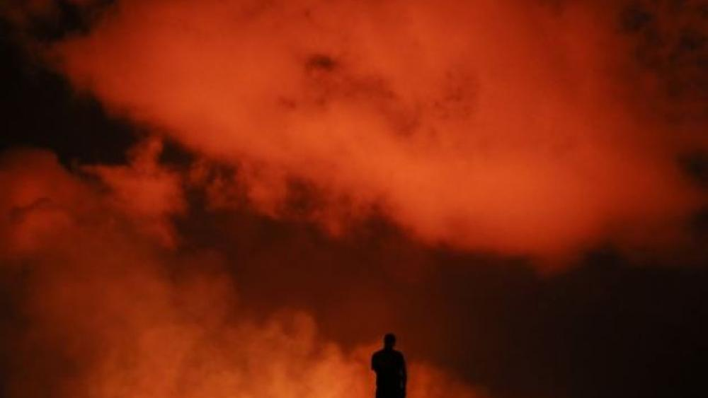 Peter Vance, 24, photographs lava erupting in the Leilani Estates subdivision near Pahoa, Hawaii Friday, May 18, 2018. AP Photo.