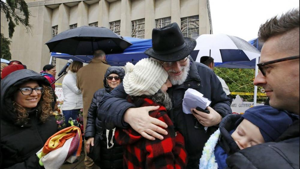 Rabbi Chuck Diamond, center, a former Rabbi at the Tree of Life Synagogue, hugs a woman after leading a Shabbat service outside the Tree of Life Synagogue, Saturday, Nov. 3, 2018 in Pittsburgh. AP Photo.
