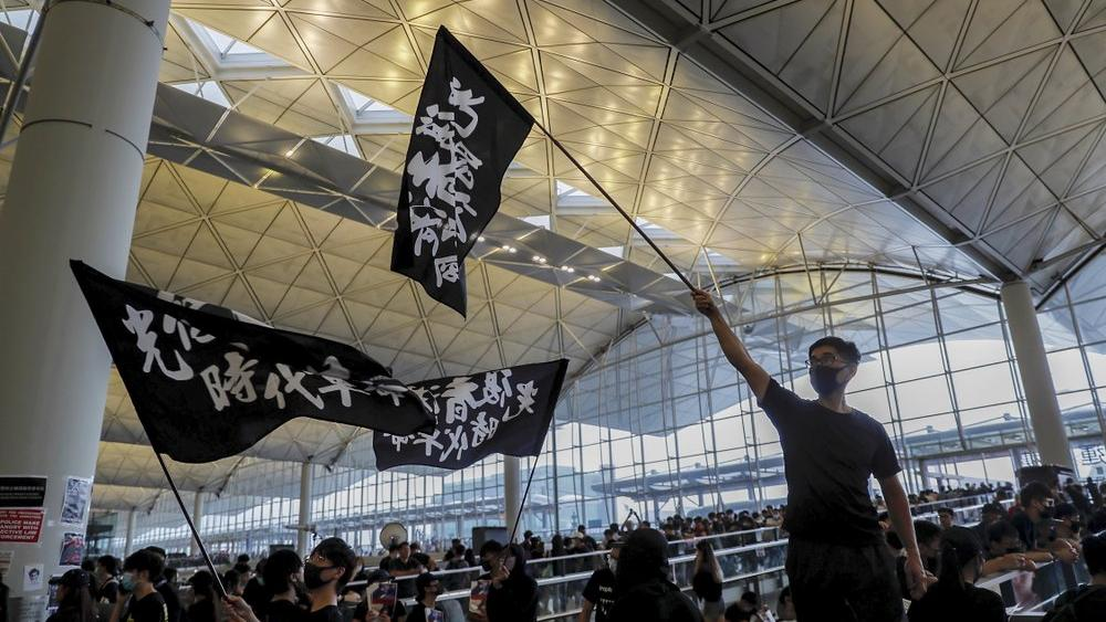 Protesters wave flags at the Hong Kong International Airport, Monday, Aug. 12, 2019 (AP Photo/Kin Cheung)