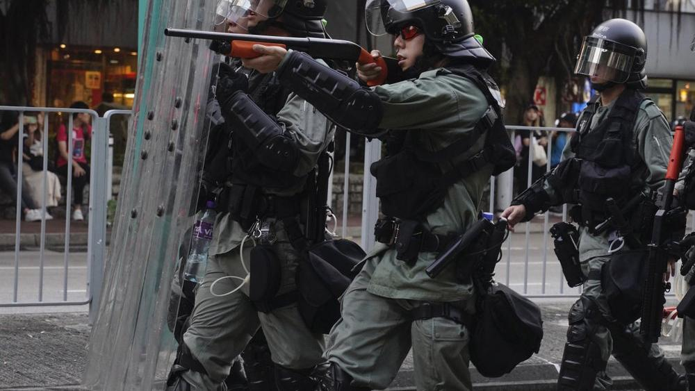 A police officer points his weapon at protesters in Hong Kong on Saturday, Sept. 21, 2019 (AP Photo/Vincent Yu)