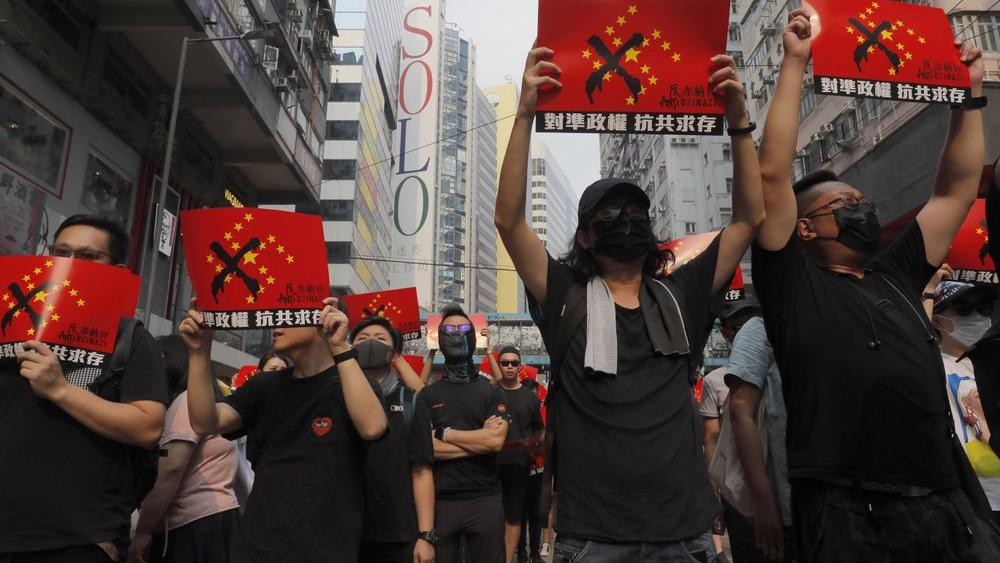 """Protesters march holding signs which reads """"Anti-Chinazi"""" combining the elements of the Nazi swastika and Chinese flag in Hong Kong on Sunday, Sept. 29, 2019 (AP Photo/Kin Cheung)"""