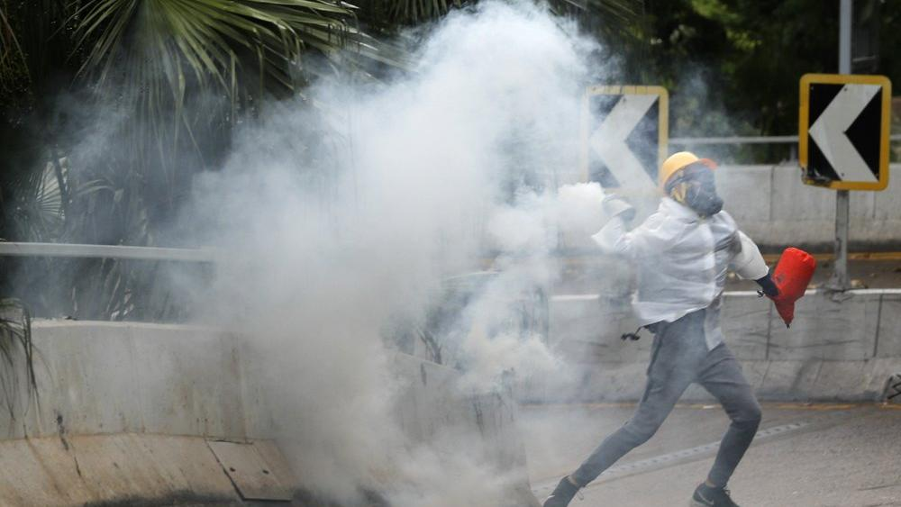 Protesters throw back tear gas at police in Hong Kong, Sunday, Oct. 6, 2019 (AP Photo/Vincent Thian)