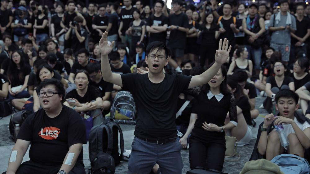 Pro-democracy protesters sing after a march against an extradition bill outside Legislative Council in Hong Kong on June 16, 2019. (AP Photo)
