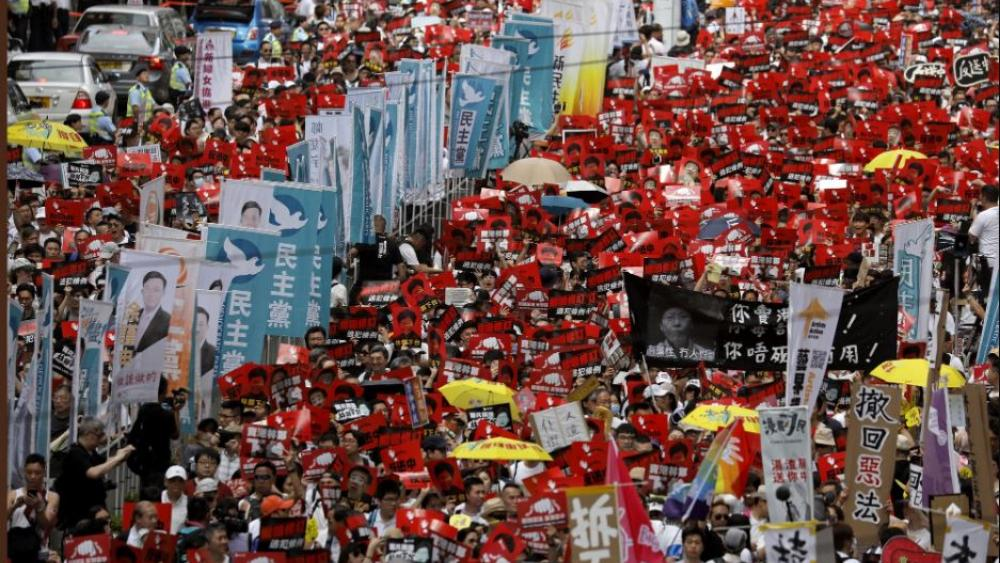 Protesters march along a downtown street against the proposed amendments to an extradition law in Hong Kong Sunday, June 9, 2019. (AP Photo/Vincent Yu)
