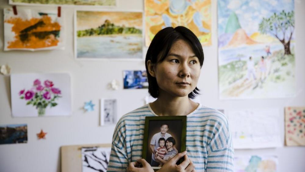 In this May 9, 2018 photo, Hua Qu, the wife of detained Chinese-American Xiyue Wang, poses for a photograph with a portrait of her family in Princeton, N.J. (AP Photo)