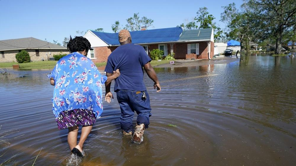 Soncia and Patrick King walk through the flooded street to their home in Lake Charles, La., Saturday, Oct. 10, 2020, after Hurricane Delta (AP Photo/Gerald Herbert)