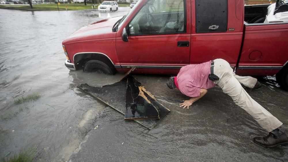Felipe Morales works on getting his truck out of a ditch filled with high water during a rain storm stemming from rain bands spawned by Tropical Storm Imelda on Tuesday, Sept. 17, 2019, in Houston. (Brett Coomer/Houston Chronicle via AP)