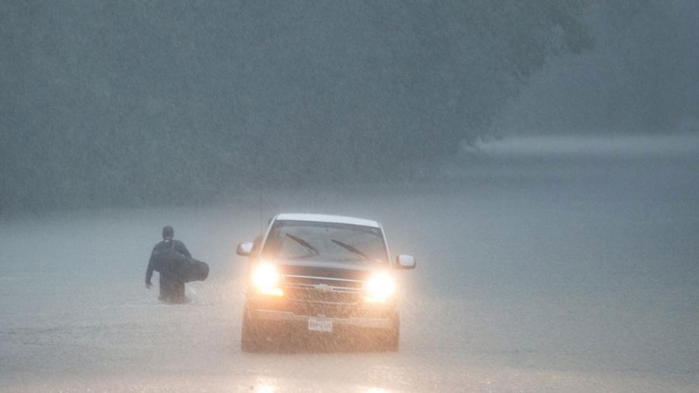 A man walks into high water into his neighborhood as rain from Tropical Depression Imelda inundated the area on Thursday, Sept. 19, 2019, near Patton Village, Texas. (Brett Coomer/Houston Chronicle via AP)