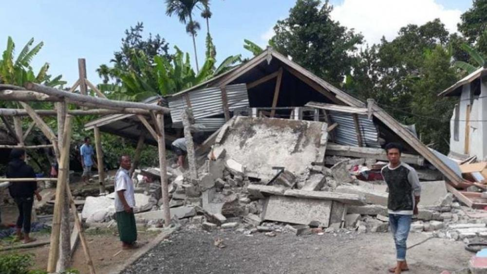Villagers walk near destroyed homes in an area affected by the early morning earthquake at Sajang village, Sembalun, East Lombok, Indonesia, Sunday.
