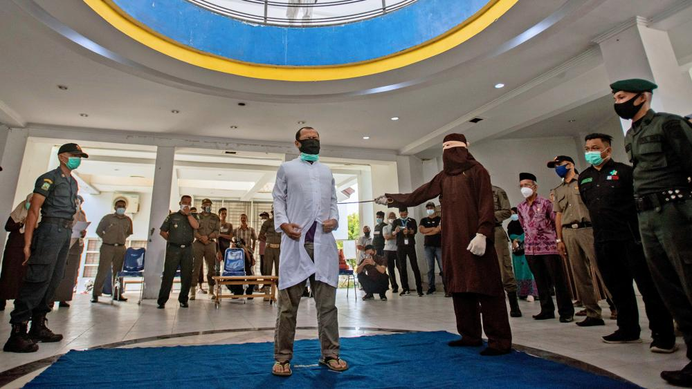 A Shariah Law official uses a rattan cane to whip a men convicted of breaking Islamic law in Banda Aceh, Aceh province, Indonesia, Jan. 28, 2021. (AP photo/Riska Munawarah)