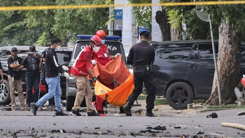 Police and rescue workers outside a church where an explosion went off in Makassar, South Sulawesi, Indonesia, Sunday, March 28, 2021. (AP Photo/Masyudi S. Firmansyah)