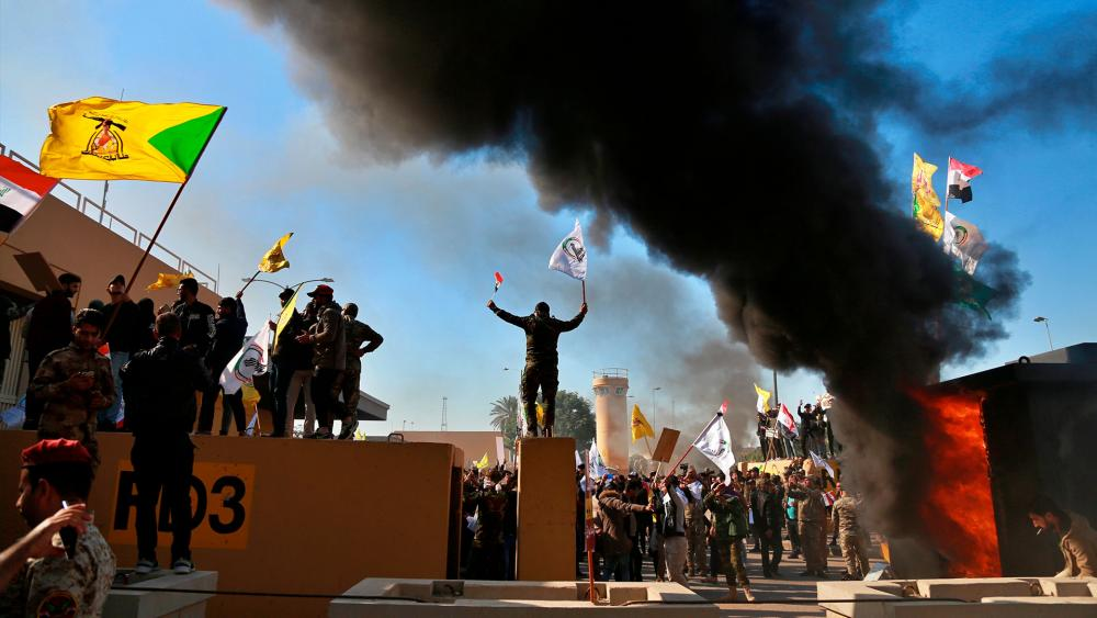 Protesters burn property in front of the U.S. embassy compound, in Baghdad, Iraq, Dec. 31, 2019 after dozens of angry Iraqi Shiite militia supporters broke into the U.S. Embassy compound in Baghdad. (AP Photo/Khalid Mohammed)
