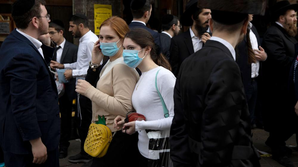 Jewish ultra-Orthodox girls wear face masks during celebrations of the Jewish festival of Purim in Bnei Brak, Israel, Tuesday, March 10, 2020. The Jewish holiday of Purim commemorates the Jews' salvation from genocide in ancient Persia.