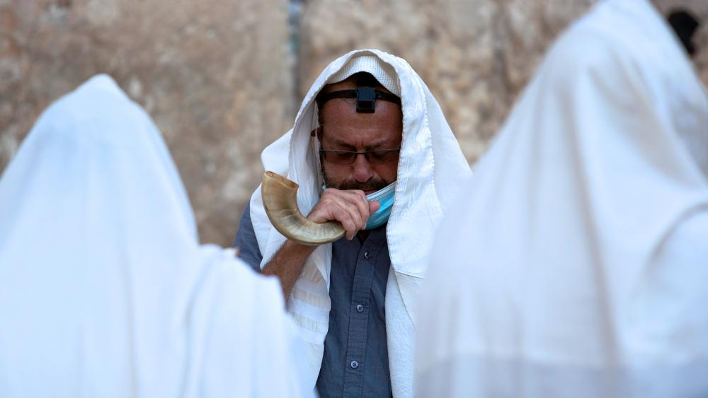 An ultra-Orthodox Jewish man blows a shofar, a musical instrument made from an animal horn, as he prays ahead of the Jewish new year at the Western Wall.(AP Photo/Sebastian Scheiner)