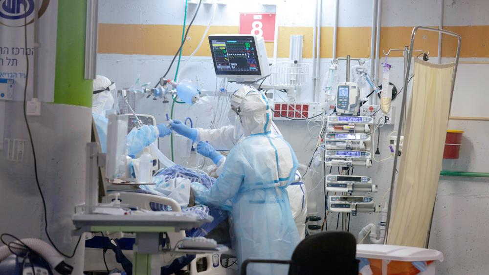 Medical professionals in full protective equipment tend to an elderly man on a ventilator in the critical care. Ramat Gan, Israel, Wednesday, Sept. 30, 2020, amid a spike in COVID-19 cases. (AP Photo/Maya Alleruzzo)