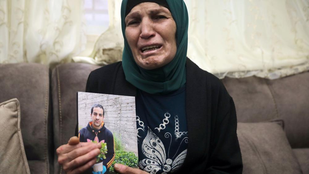 Rana, mother of Iyad Halak, 32, holds his photo at their home in eastern Jerusalem's Wadi Joz, Saturday, May 30, 2020