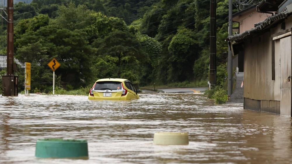 A car is stuck in a flooded road by heavy rain in Yatsushiro, Kumamoto prefecture, southwestern Japan, Saturday, July 4, 2020 (Kyodo News via AP)