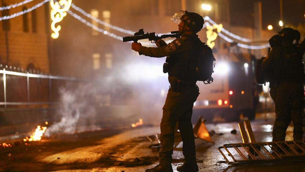 An Israeli police officer aims his rifle towards Palestinian demonstrators during clashes at Damascus Gate just outside Jerusalem's Old City, Saturday, May 8, 2021. (AP Photo/Oded Balilty)