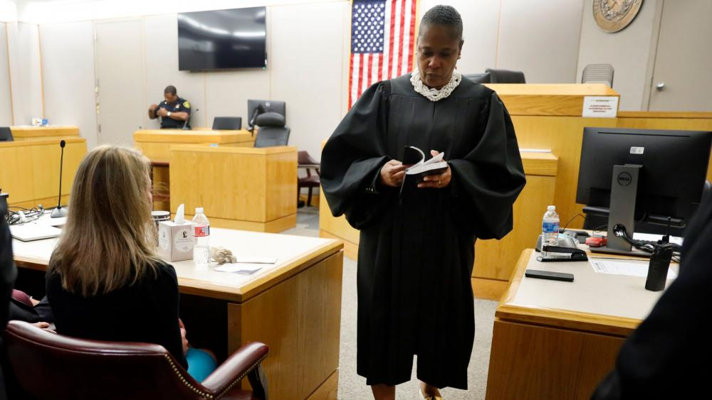State District Judge Tammy Kemp opens a Bible to John 3:16 before giving it to former Dallas Police Officer Amber Guyger, left, before Guyger left for jail, Wednesday, Oct. 2, 2019, in Dallas. (Tom Fox/The Dallas Morning News via AP, Pool)