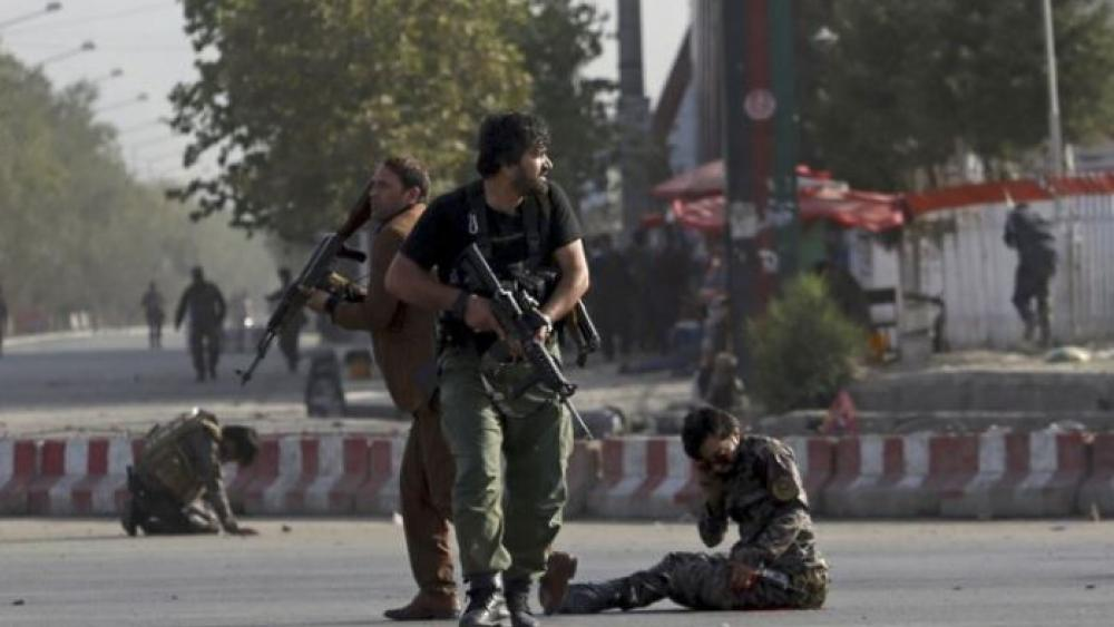 Afghan security personnel stand guard next to wounded comrades at the site of an attack near the Kabul International Airport, in Kabul, Afghanistan, Sunday, July 22, 2018.