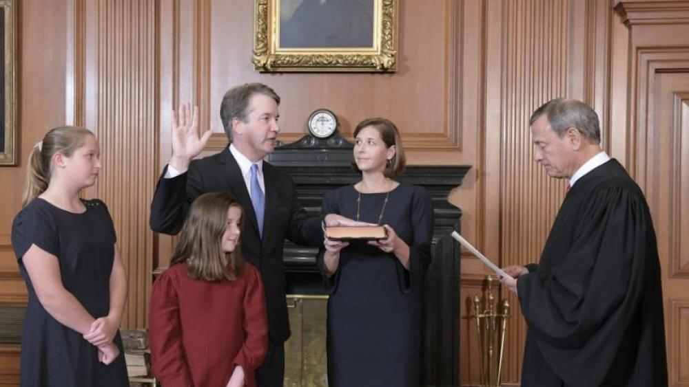 Chief Justice John Roberts, right, administers the Constitutional Oath to Judge Brett Kavanaugh in the Justices' Conference Room of the Supreme Court Building. Ashley Kavanaugh holds the Bible.