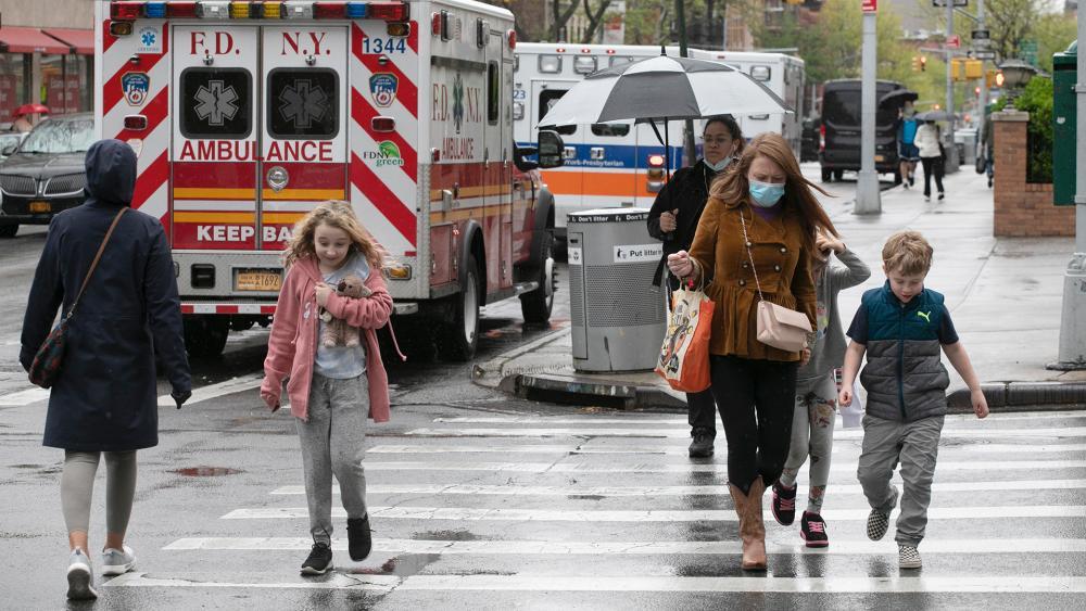 A family walks by ambulances parked outside NewYork–Presbyterian Brooklyn Methodist Hospital, May 6, 2020 in New York during the coronavirus pandemic. (AP Photo/Mark Lennihan)