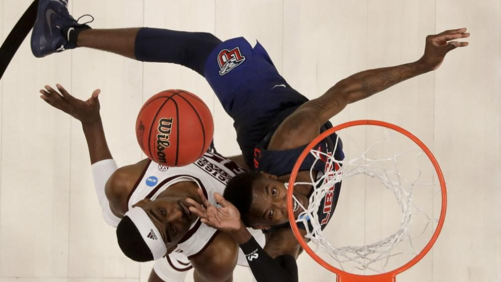 Liberty guard Lovell Cabbil Jr., right, shoots over Mississippi State forward Aric Holman during the second half of a first-round game in the NCAA men's college basketball tournament Friday, March 22, 2019, in San Jose, Calif. (AP Photo/Ben Margot)